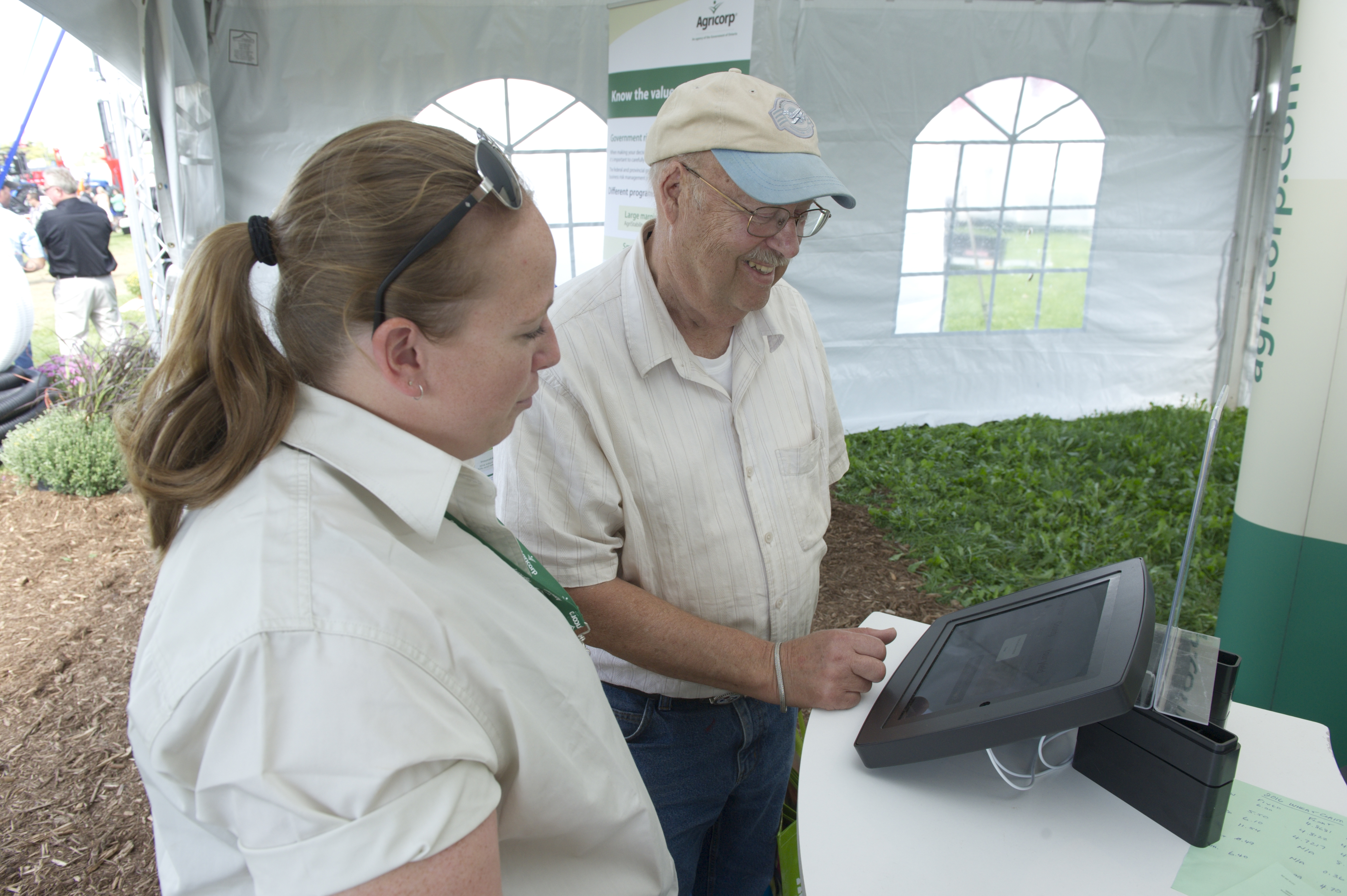 An Agricorp staff member helps a producer use a kiosk to access information at a farm show.
