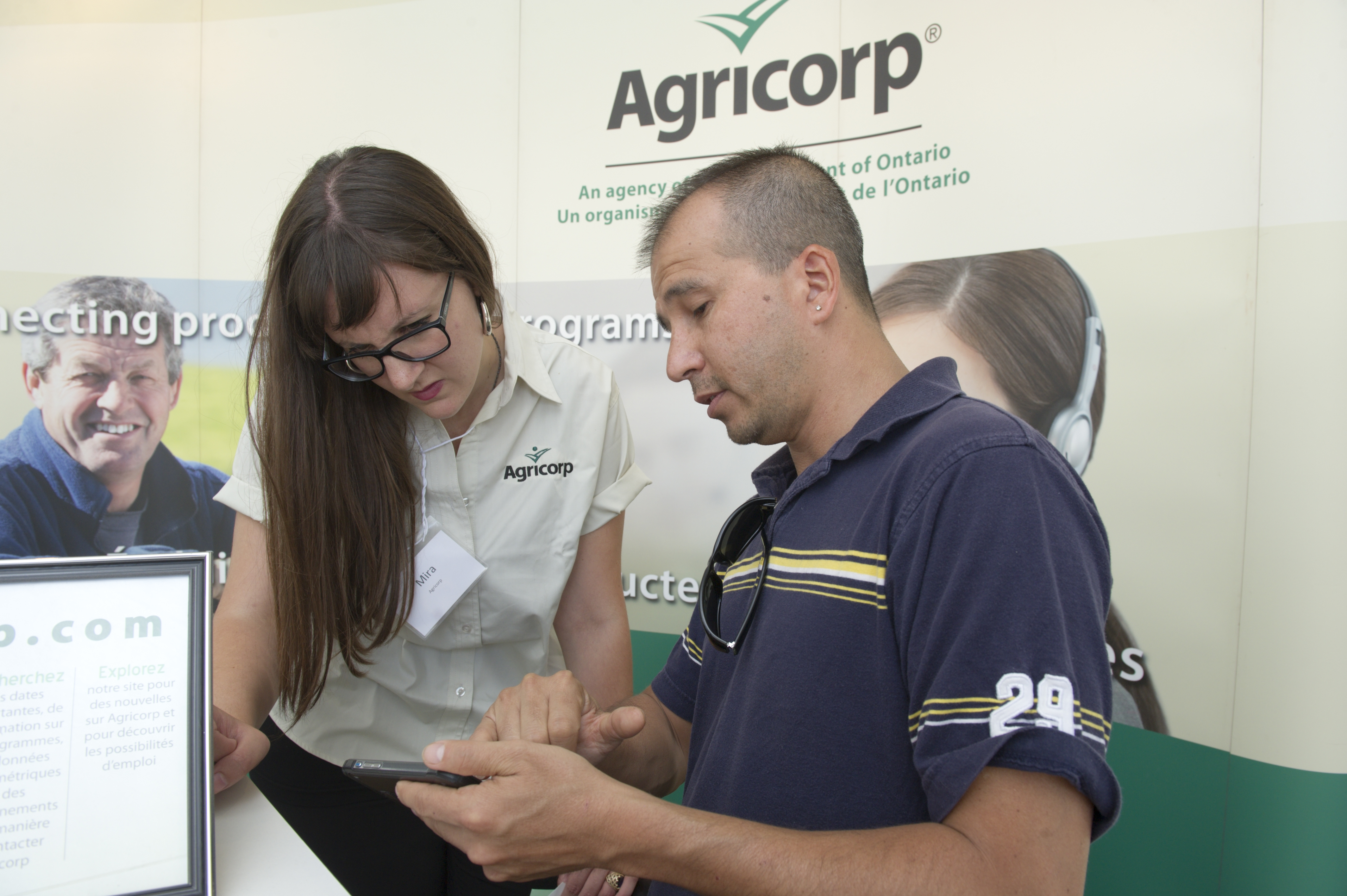 A producer shows an Agricorp staff member something on his phone at a farm show.