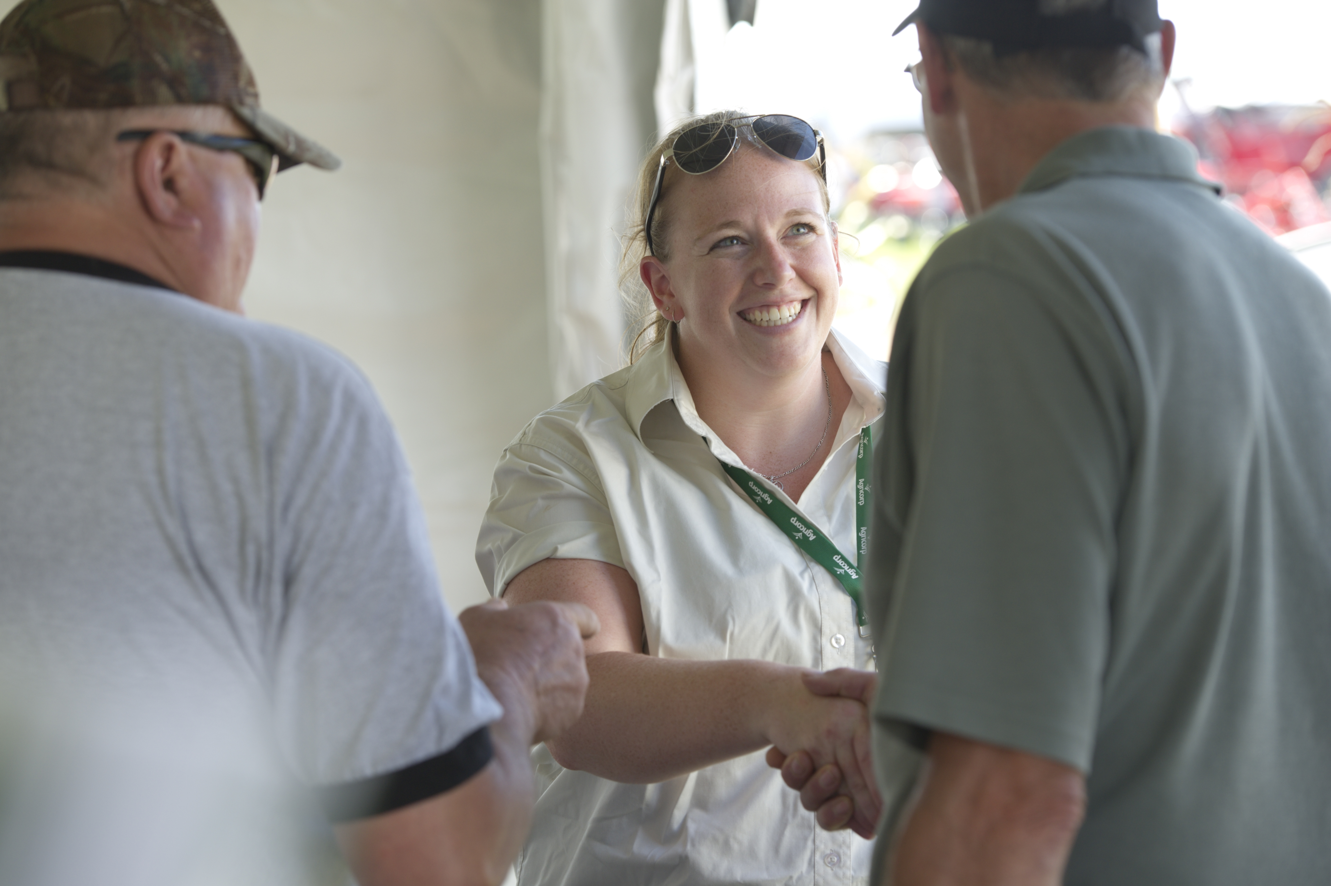 An Agricorp staff member shakes hands with a producer at a farm show.