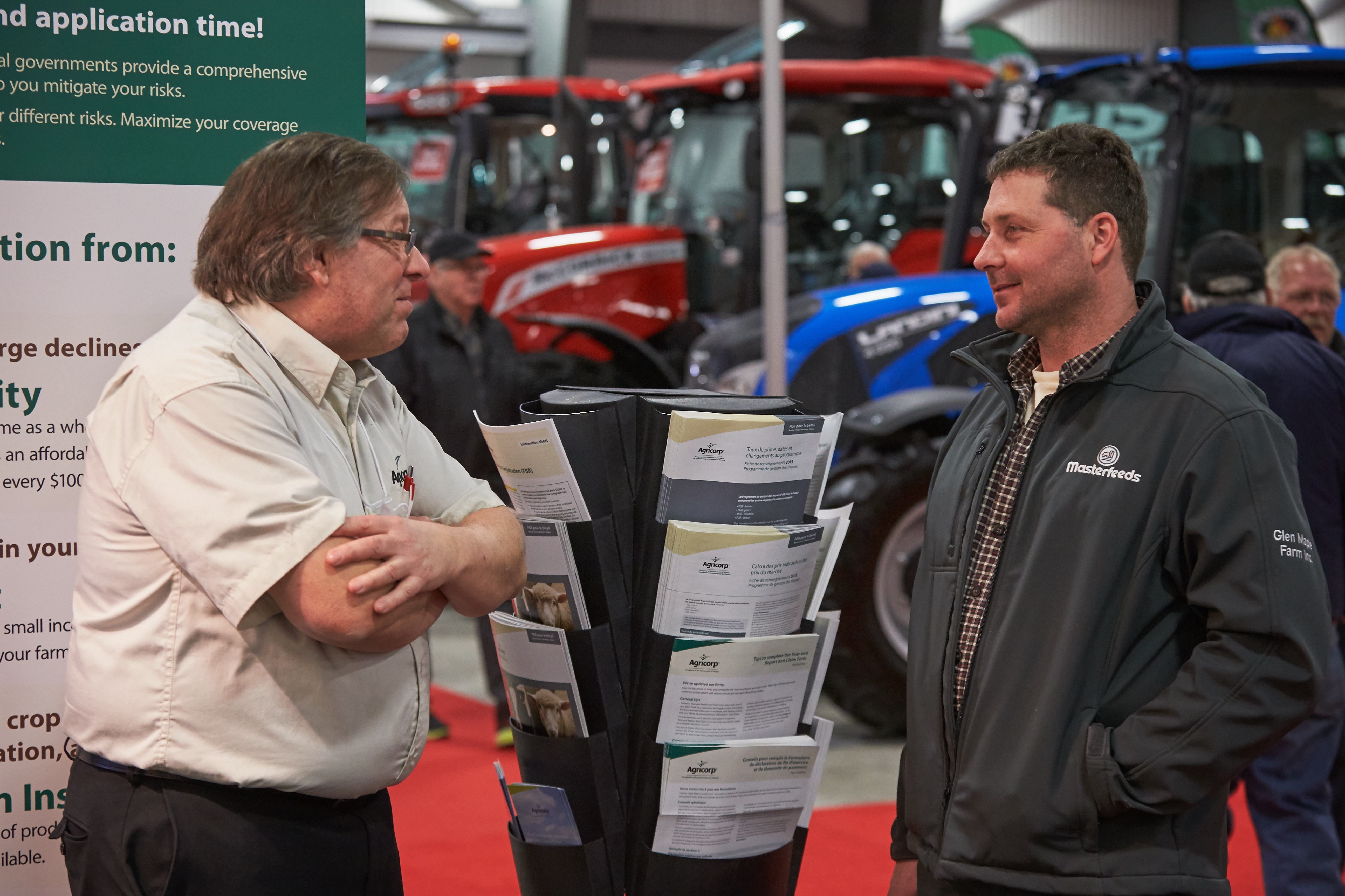 An Agricorp staff member talks with a producer at a farm show.